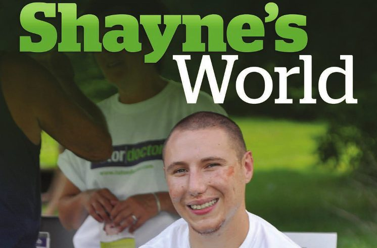 Shayne's World - Shayne sit outside under a palm tree with wide smiles