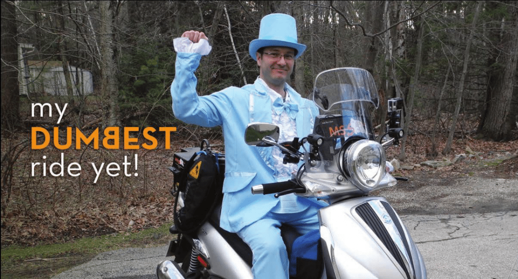 My Dumbest Ride Yet: Paul sports a light blue tuxedo and tophat while riding his motorcycle.