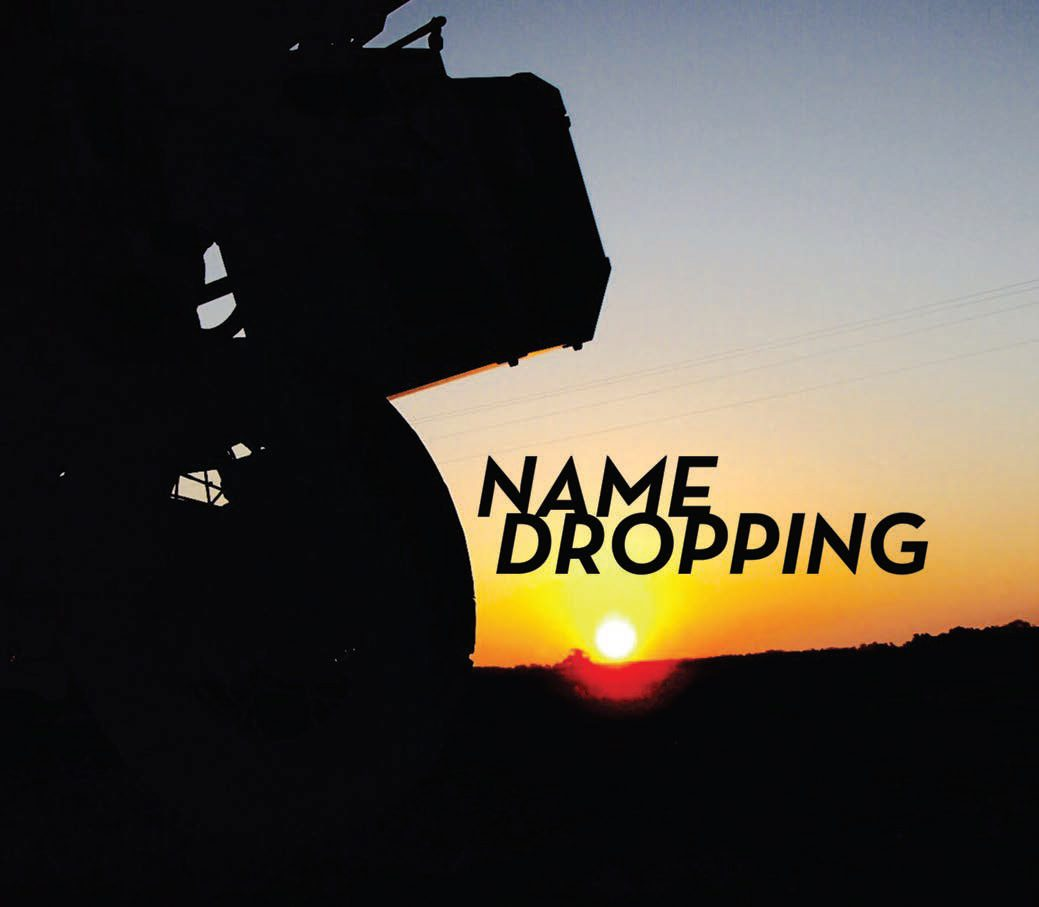 Title: Name Dropping. Dark image of the back of a motorcycle wheel with a sunseting just on the horizon behind it.