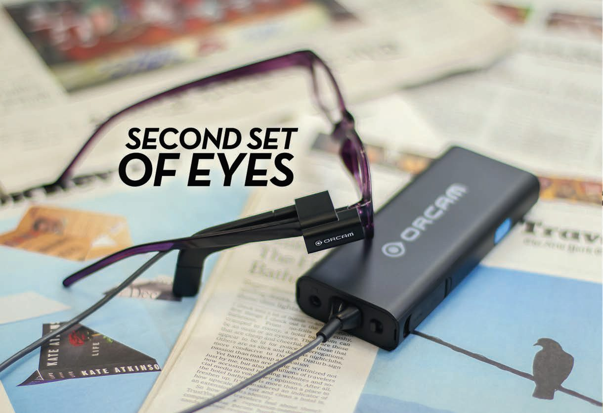 Second Set of Eyes- Image of a OrCam's MyEye device attached to a pair of glasses lying on print magazines