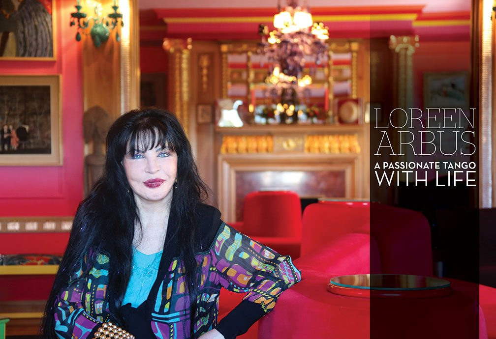 Image: Loreen Arbus with a glowing smile seated with a backdrop of a glowing in the warmth of a vibrant reds and golds of her home in New York City.