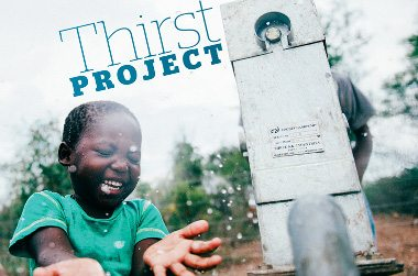 Thirst Project. Image of a young boy laughing while catching water in his hands under a working water pump