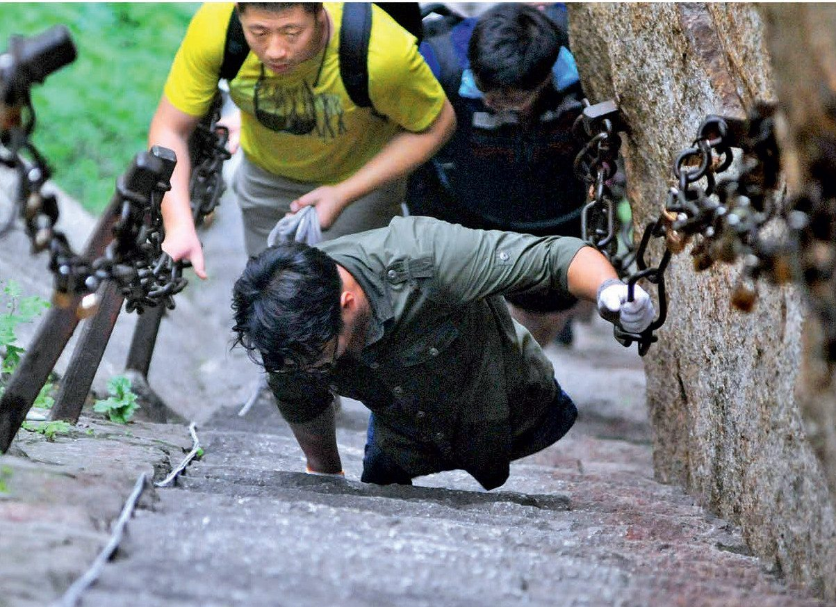 Chen Zhou makes ascent up stairs of rock by pulling himself up holding on to large chains, while other hikers follow him.
