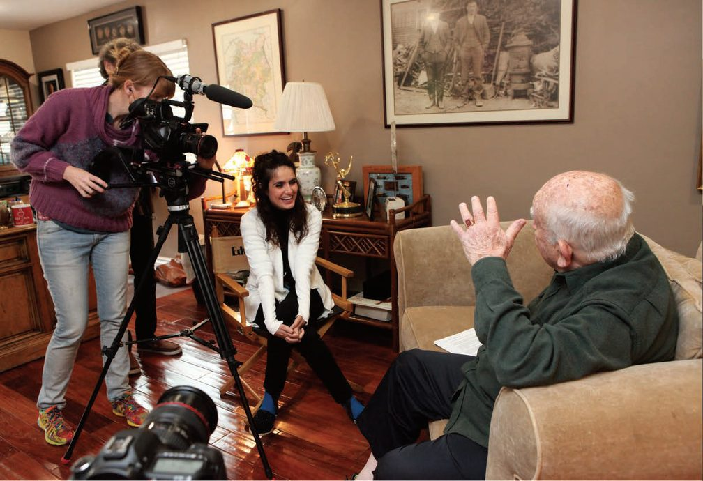 Asner's seated on couch sharing laughs with Lia Martirosyan (opposite) while being filmed by videographer