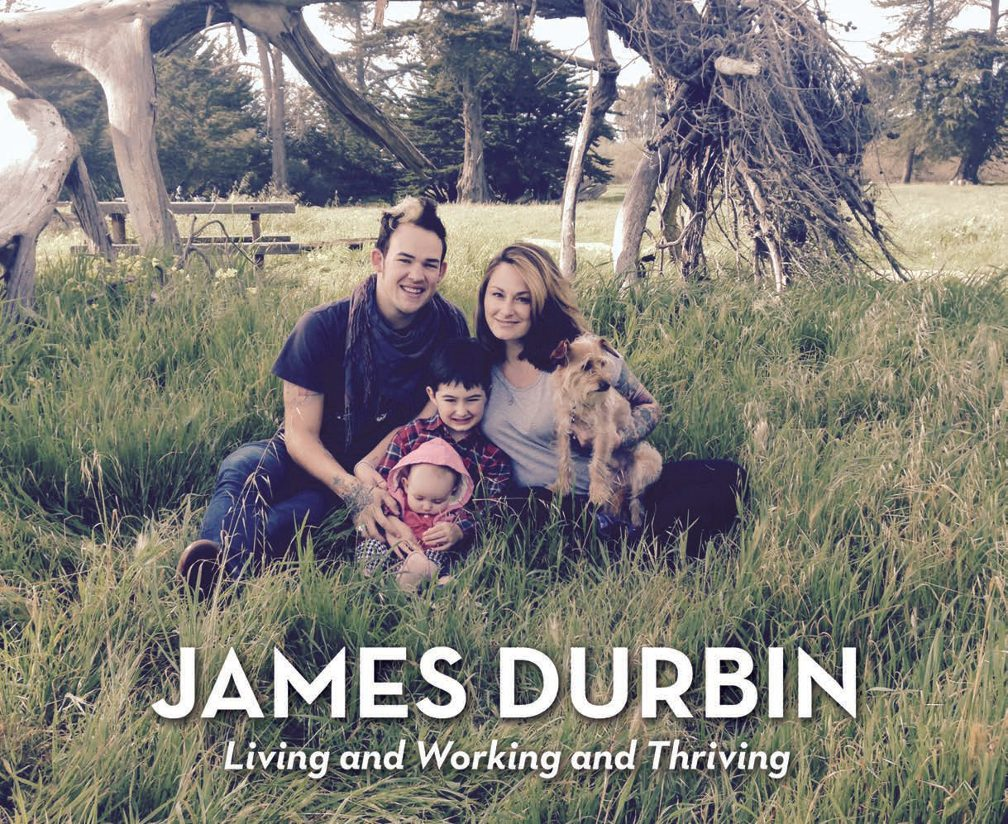 Title James Durban- Living and Working and Thriving. Image of Durban, his wife, young son, baby girl and dog sitting under trees in a long grass