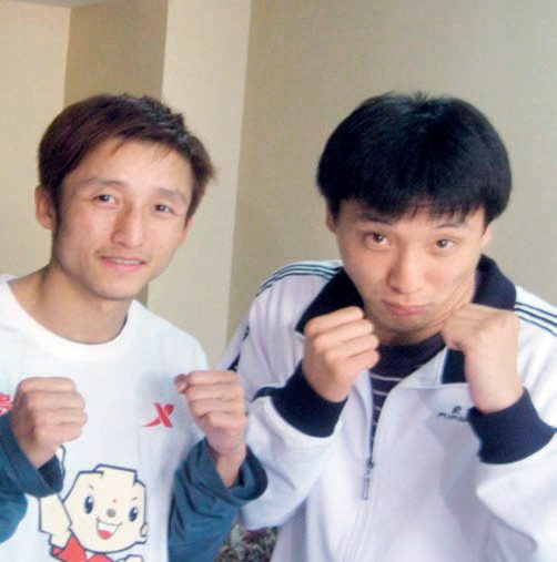 Image of Wang Quiang and fellow boxer facing the camera with fists up and in street clothes.