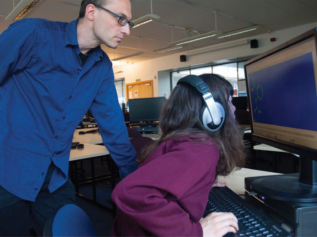 Image: Dr. Volker looking over the should of young female student who is seated, looking intently at a computer screen