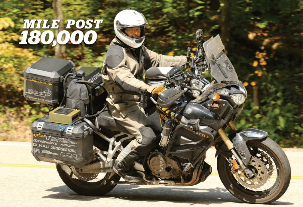 Title: Mile Post 180,000. Image: Long Haul Paul Riding his Motorcycle with protective gear.