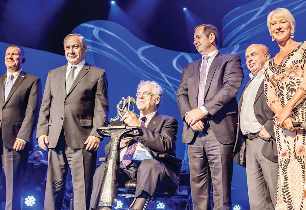 Itzhak Perlman seated on scooter, holding award surrounded by dignitaries.