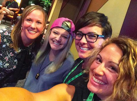 Ashley Fiolek smiling with three friends at the National Association of the Deaf Conference