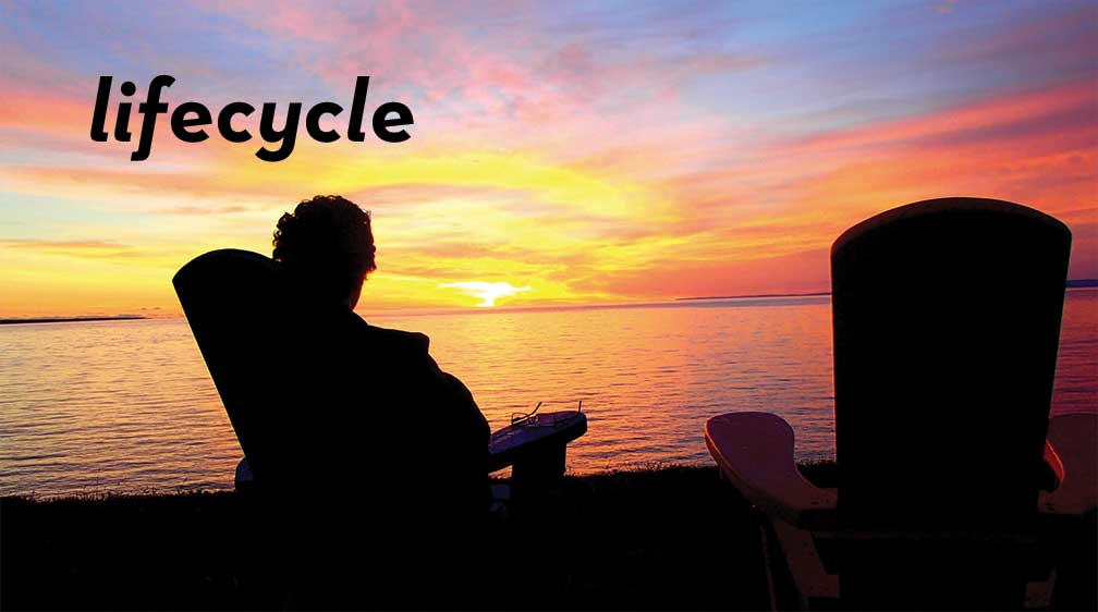 Paul sits in a highback chair by the lake and watches the warm colors of the sun striping the sky at sunset.