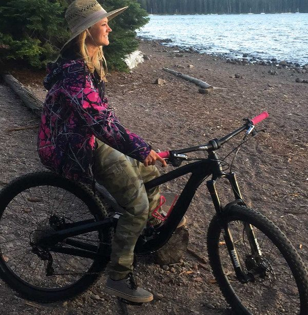 Ashley, wearing a sunhat and street clothes, sits on her mountain bike while looking out over a river.