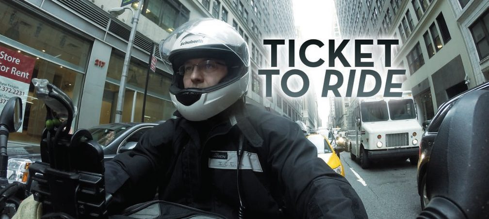 Title: Ticket to Ride. Selfie of Paul on his motorcycle in rainy city traffic followed by a yellow cab.
