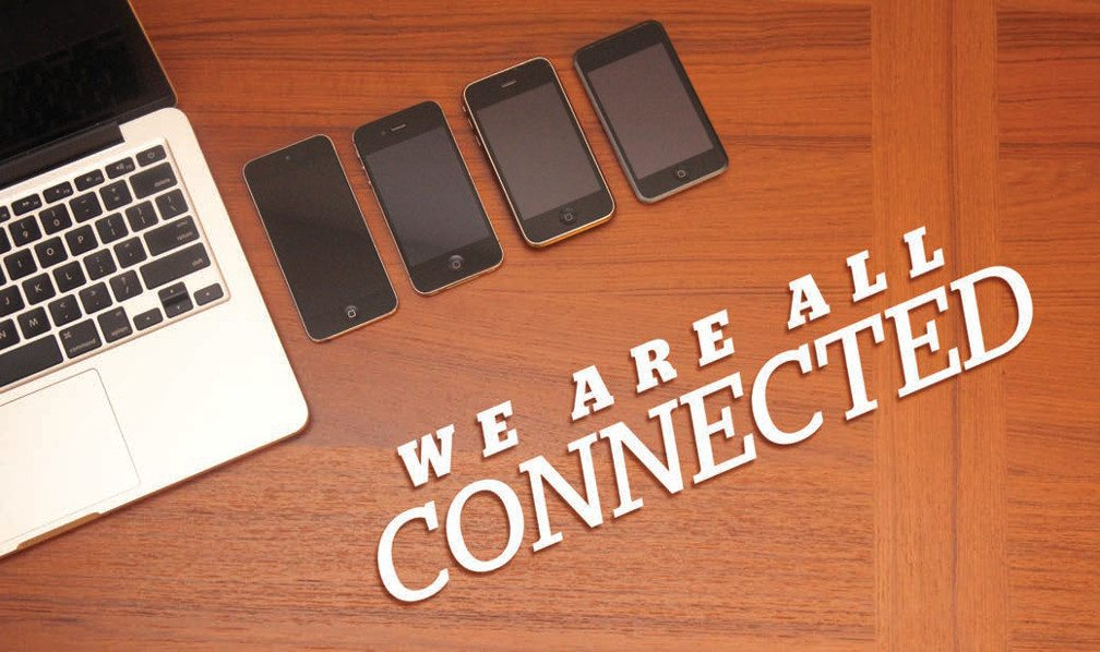 Title: We are all connected. Image The top of a wooden desk lined with a laptop keeyboad and four smart phones.
