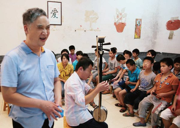 Mu Mengjie sings in front of class as a man plays the banhu, which is similar to a banjo used with a bow.