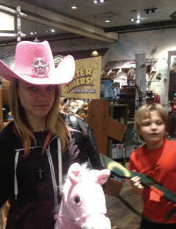 Ashley with a pink cowboy hat rides a pink hobby horse with her little brother in the background.