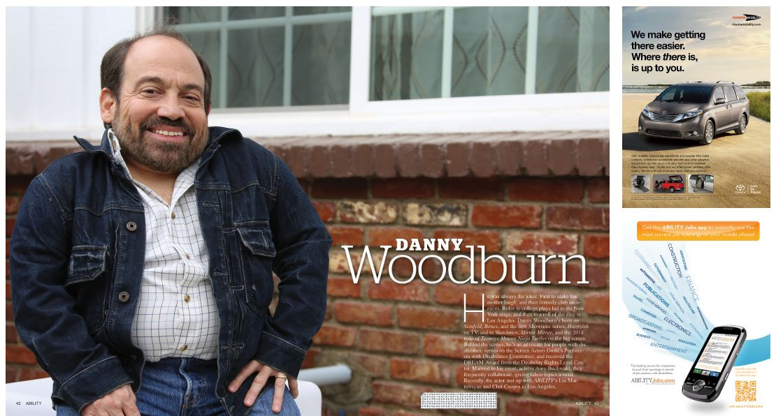 Danny Woodburn sits smiling in front of a red brick wall with white windows.