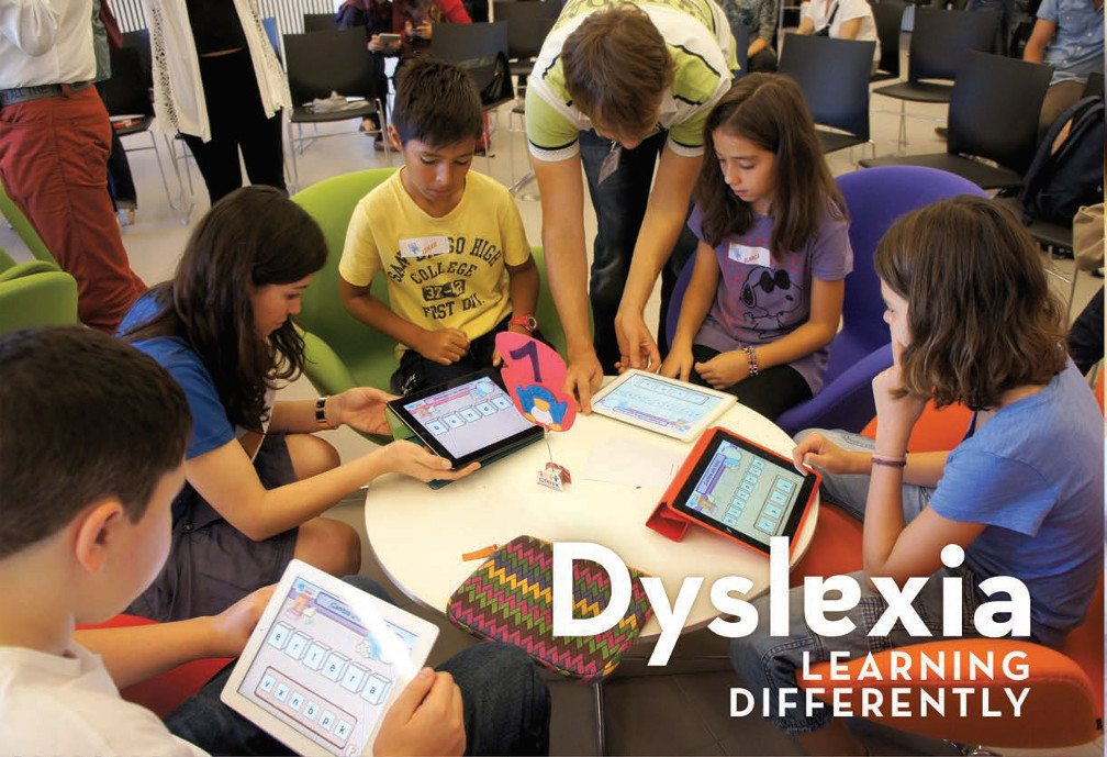 Title: Dyslexia--Learning Differently. Image of Five Boys and girls sit around a circular table working on tablets.