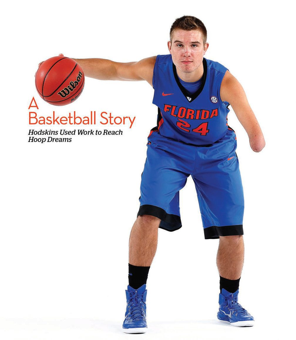 Title: Hodskins Used Work to Reach Hoop Dreams. Image: Zach in a blue basketball uniform dribbles basket ball at shoulder height, facing the camera.