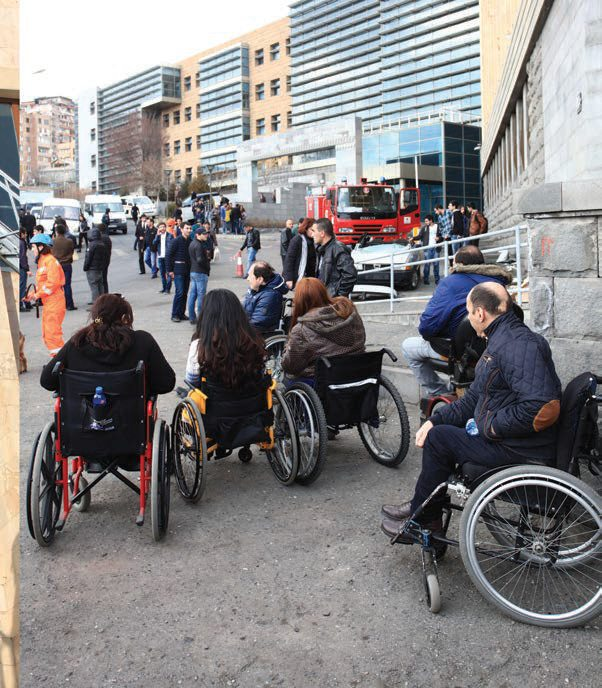 people-in-wheelchairs-gather-outside-building with back drop of people standing in the street in front of other buildings..