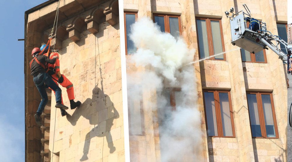 Left: Men-hang-from-building-during emergency evacuation drill. Right: Mechanical fire-equipment shoot water at side of building during drill.