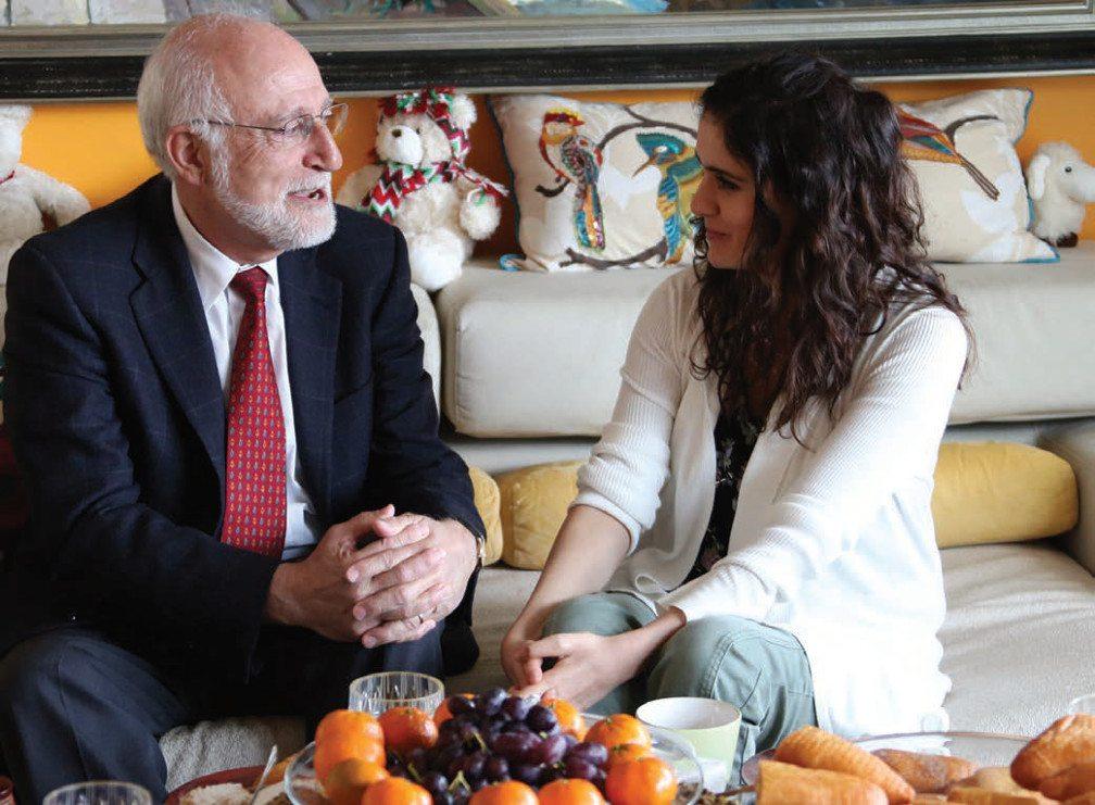 dr-der-kiureghian-lia-martirosyan-talk while sitting on a pillowed sofa, foreground coffee table with fresh fruit bowl
