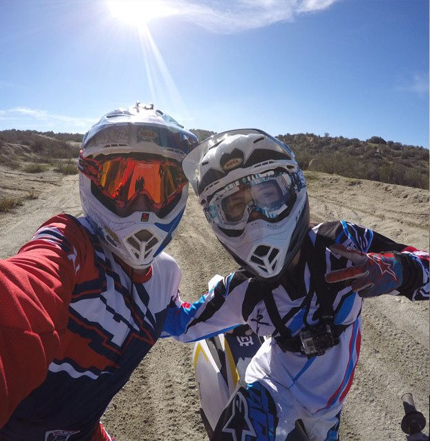 Selfie of Ashley and friend in riding gear and helmust with backdrop of dirt trail, green hills, blue sky and sun glare