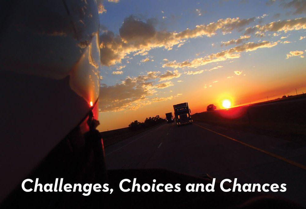 Challenges, Choices and Chances. Image of Helmut in forground with sun going down in background behind on coming tractor trailers.