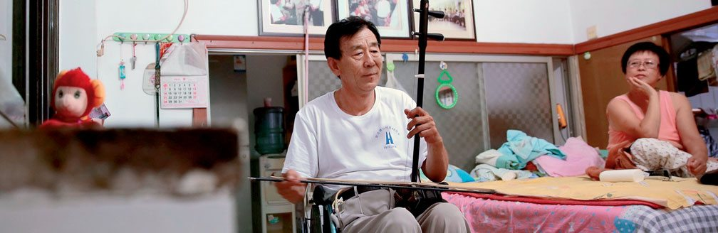 Image of man in wheel chair playing Instrument while woman looks on while sitting on a bed.