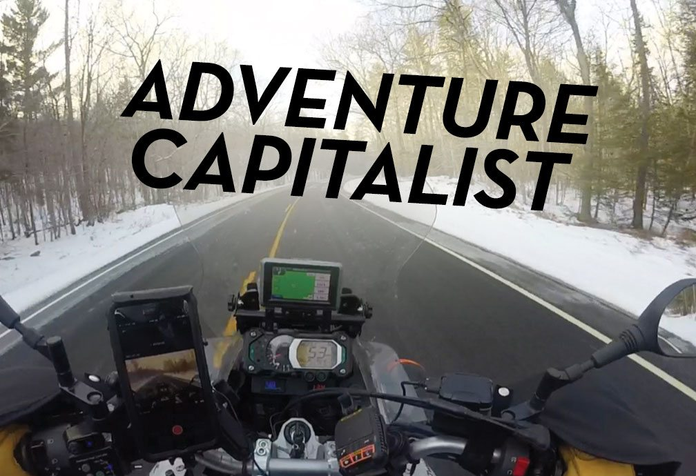 Adventure Capitalist - Image taken from Paul's perspective behind the windshield of his motorcycle on snowy day.