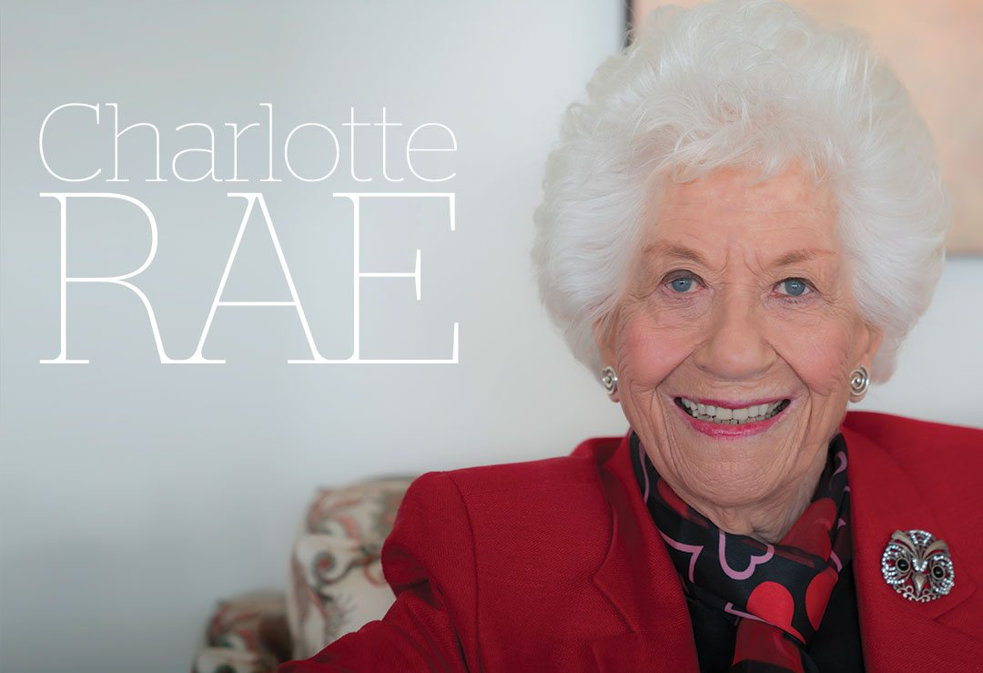 Charlotte Rae in a red blazer smiles as she sits in a flowered chair,