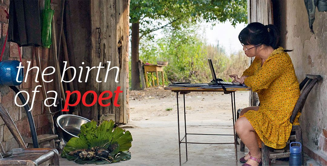 The Birth of a Poet. Image: Wearing a bright yellow flowered dress, Yu Xiuhua China types on a small laptop in rustic surroundings. Background wide open doors to outside trees and bushes.