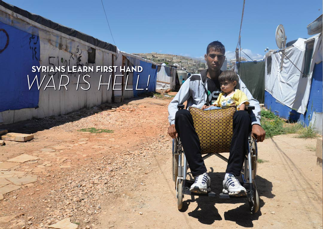 Man in wheelchair with a tiny boy and bag on his lap. Background of shelters covered in tarps.