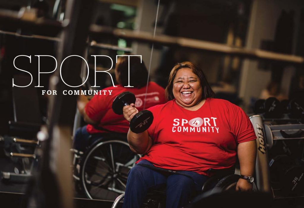 Title Sport for Community. Woman in wheelchair lifts 20 lb. dumbbell at a gym facility.