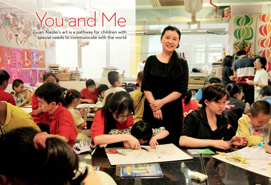 You and Me: Guan Xiaolei's art is a pathway for children with special needs to communicate with the world. Guan stands in the middle of several students working at tables.