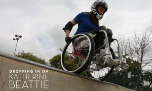 Katherine Beattie -Dropping In. Beattie in wheelchair and helmut sitting at the edge of a skateboard ramp