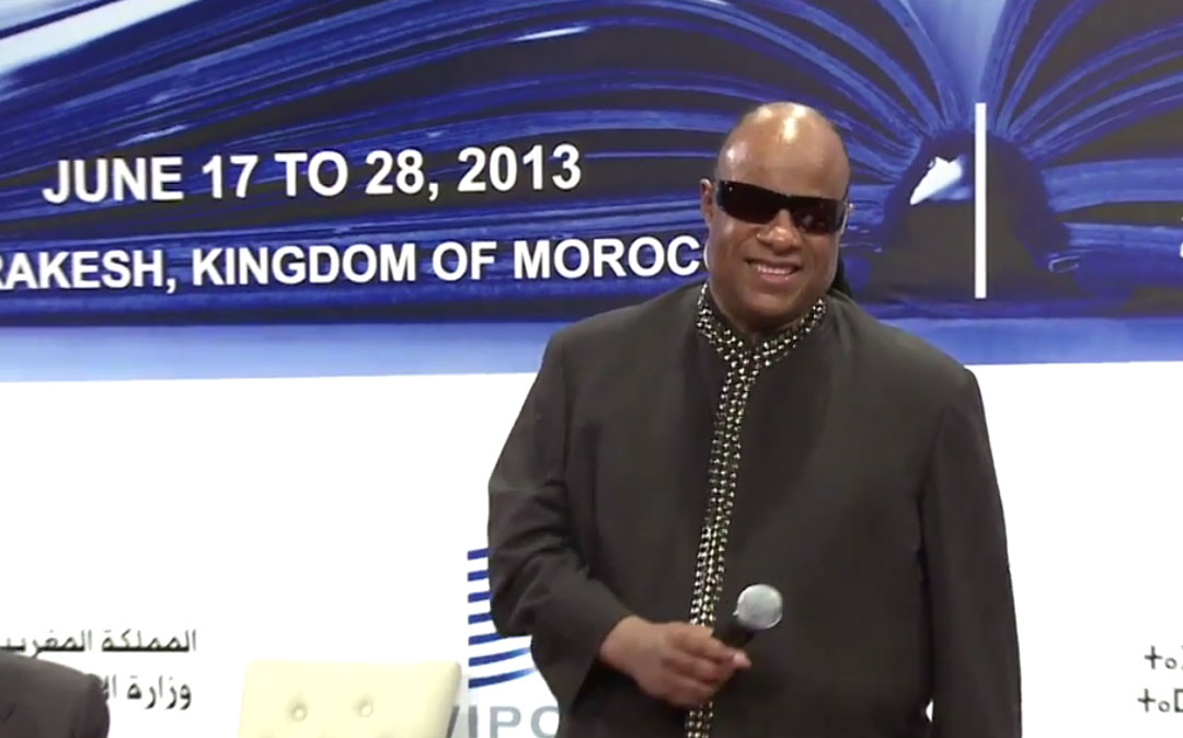 Stevie Wonder congratulates representatives from WIPO's member states and non-governmental organizations( on the adoption of the Marrakesh Treaty for the visually impaired.