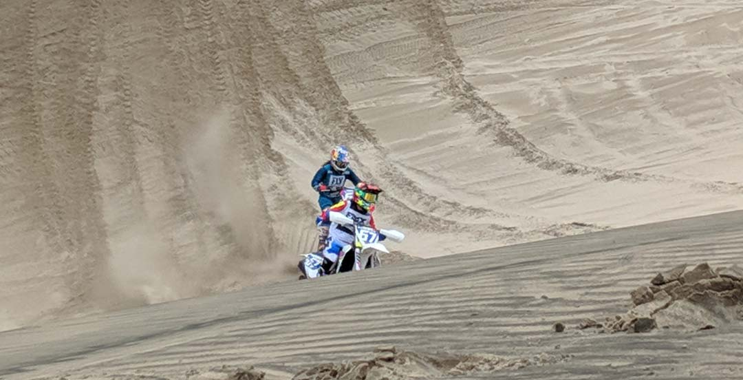 Ashley riding motorcycle down a sand dune