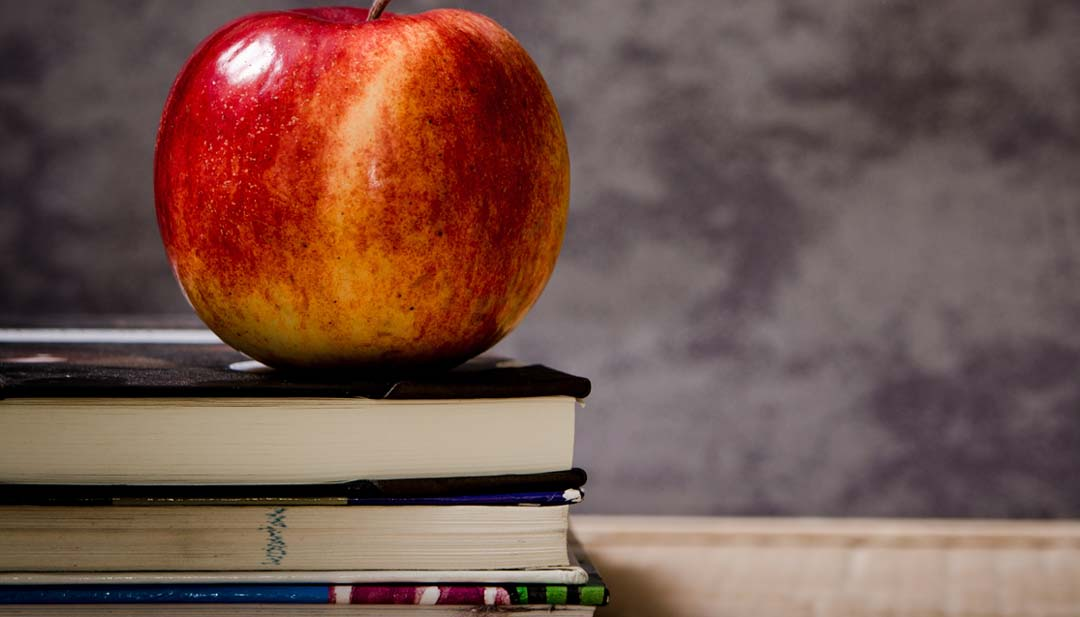 Teachers desk with apple and books