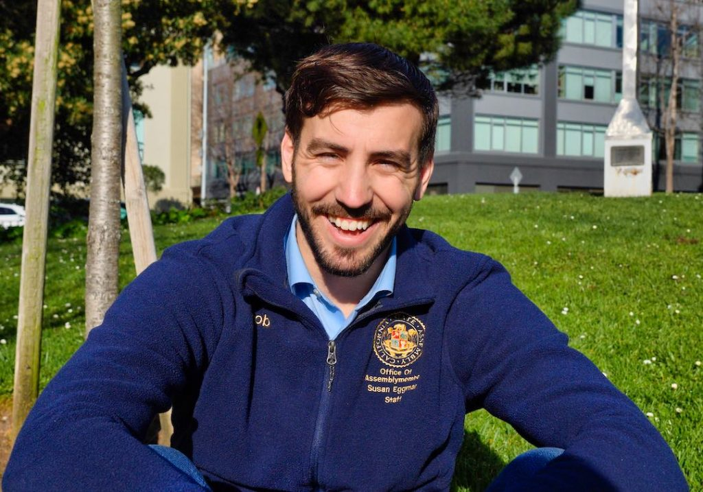 Jacob Fraker, a young man with short brown hair is standing in a park. He has a beard, wears a blue sweater and smiles. It's a sunny day.