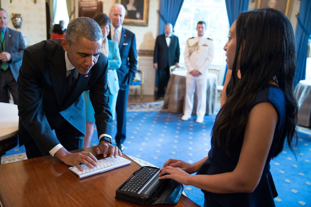 Haben, who has long black hair falling over her shoulder and wears a dark blue dress, stands at a table and has her hands on her BrailleNote to read what former President Obama, who stands on the other side of the table and wears a black suit, types on a keyboard. Lined up behind former President Obama are several people including former Vice President Biden.