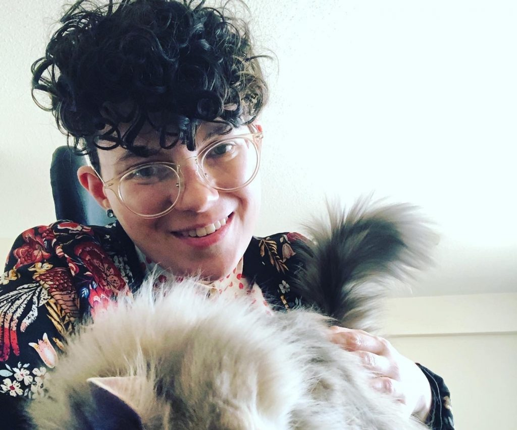Gabriel, a non-binary person with curly, short, brown hair, large, white, round glasses and a fluffy cat.