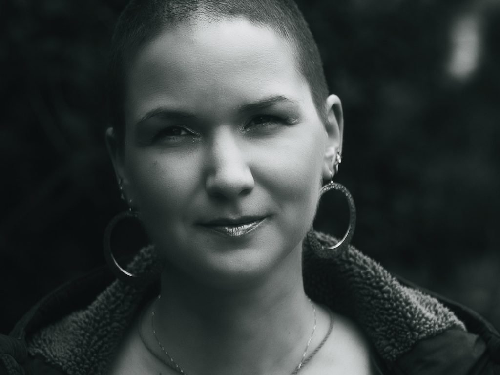 A black and white close-up shot of Karina, a woman with shaved hair and huge round earrings