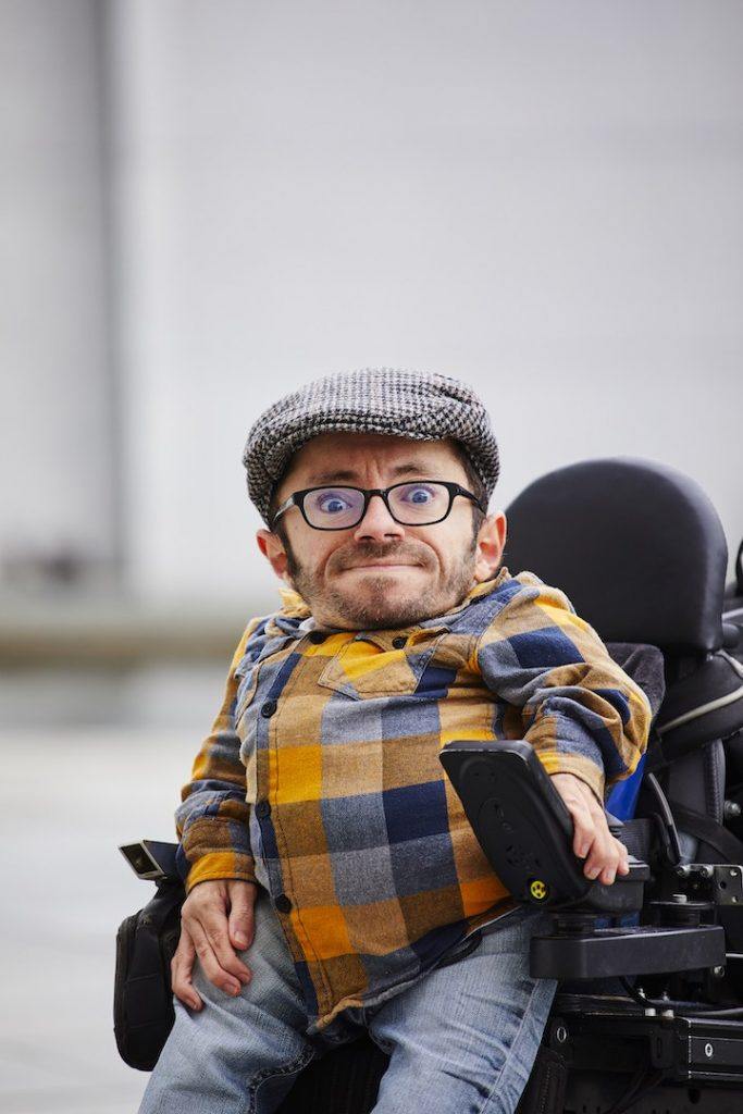 Raul, a man with short, brown hair, glasses and a hat sits in a wheelchair and smiles slightly.