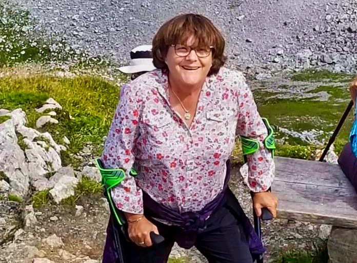 Nancy, a woman with chin-length brown hair stands on a hill. She smiles and uses green crutches.