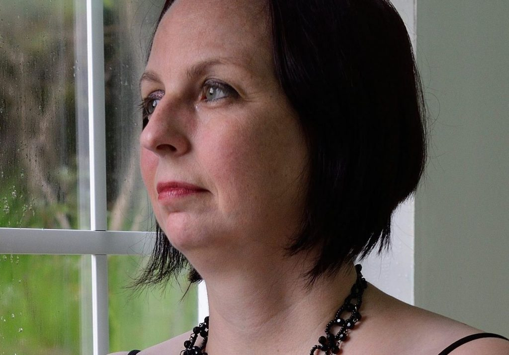 A woman with chin-length, black hair is looking out of a window.