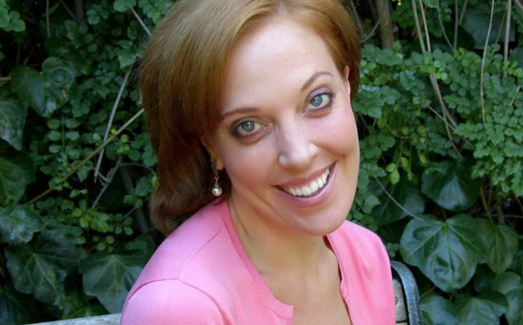Shelly, a woman with light brown hair sits on a bench. She smiles and wears a pink jacket and perl earrings.