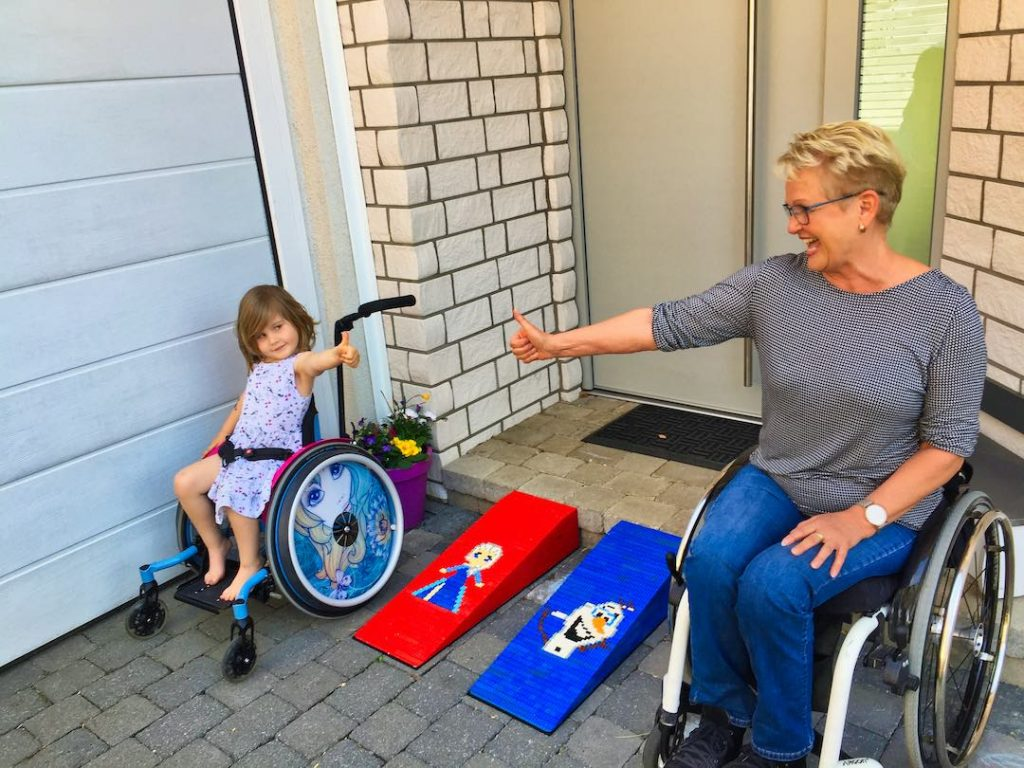 Mona loves her new 'Frozen'-themed ramp: A small child with shoulder-length brown hair in a wheelchair gives Rita, a woman with short blonde hair and also in a wheelchair, a thumbs up.