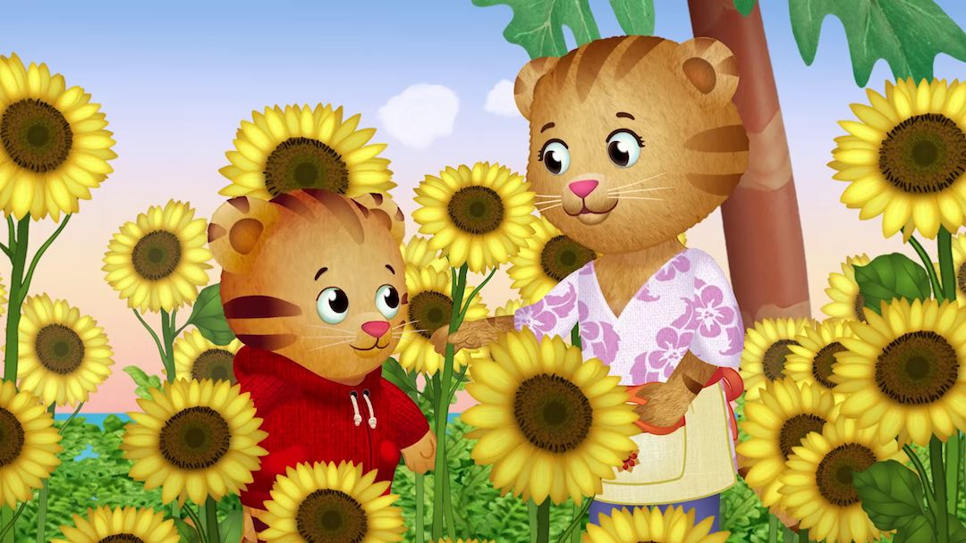 A tiger mom and Daniel Tiger stand in a field of sun flowers.
