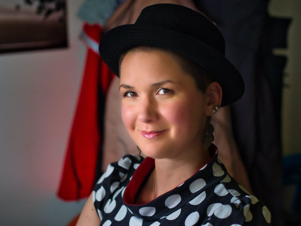 A woman with short brown hair sits in a kitchen. She is wearing a black hat, large earrings and a black shirt with white polka dots
